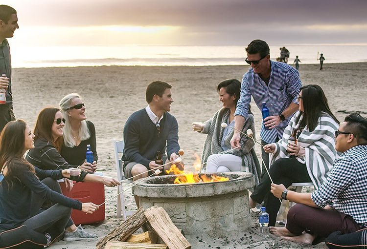 Group of friends sitting around fire pit with ocean in the back