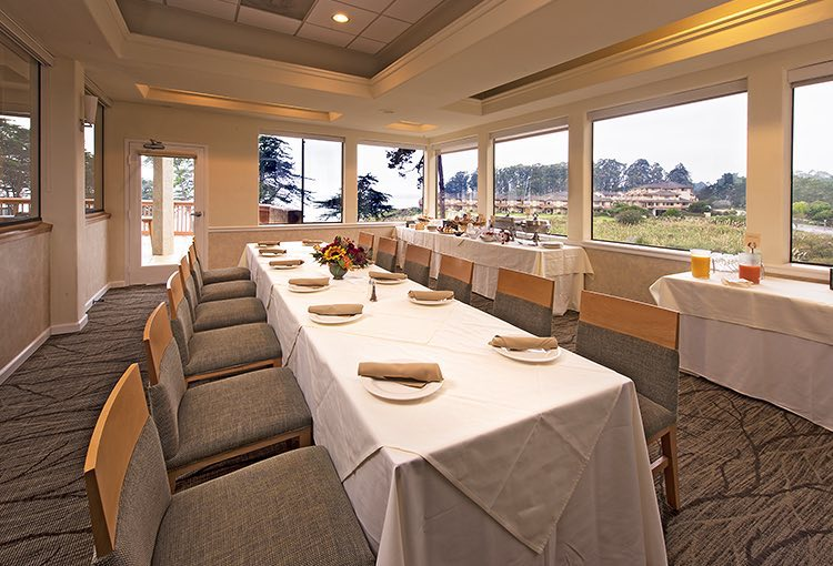 Long rectangular table with plate at each chair and buffet by window