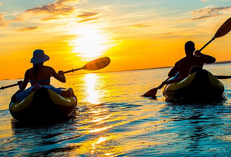 Two people kayaking into the sunset