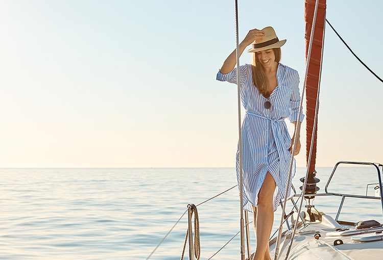 Woman wearing dress and sunhat on boat