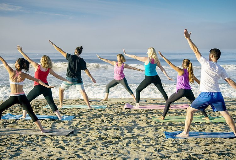 Group of people doing yoga next to the beach