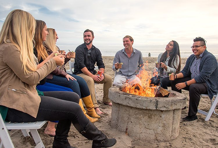 Group of friends sitting next to fireplace by the beach