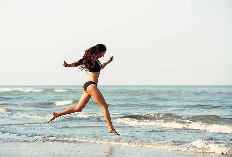 Woman jumping next to ocean shore