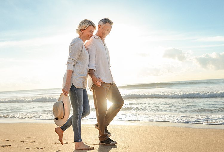 Older couple walking by the ocean shore