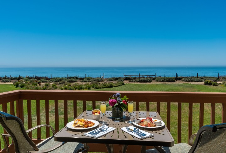Breakfast set up on patio table with two chairs overlooking the ocean