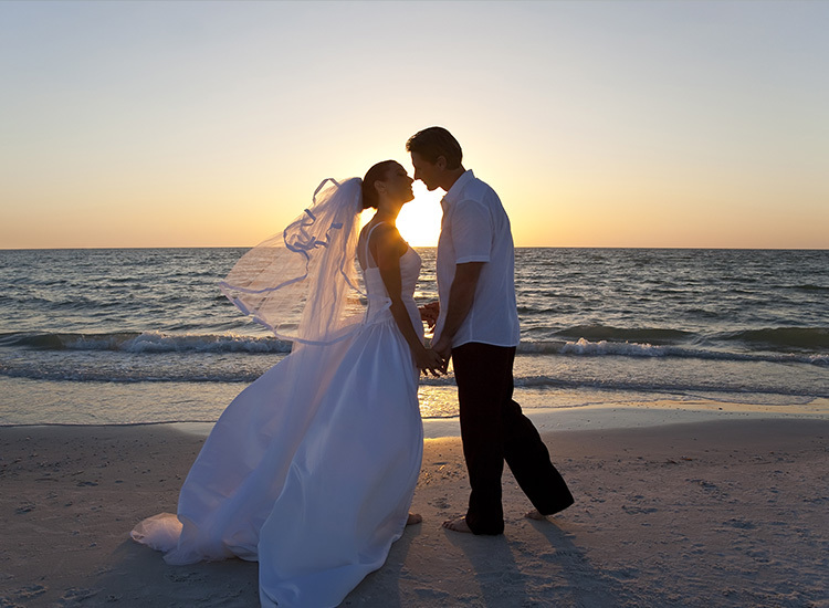 a newlywed couple posing wile sharing a kiss on the beach in wedding attire