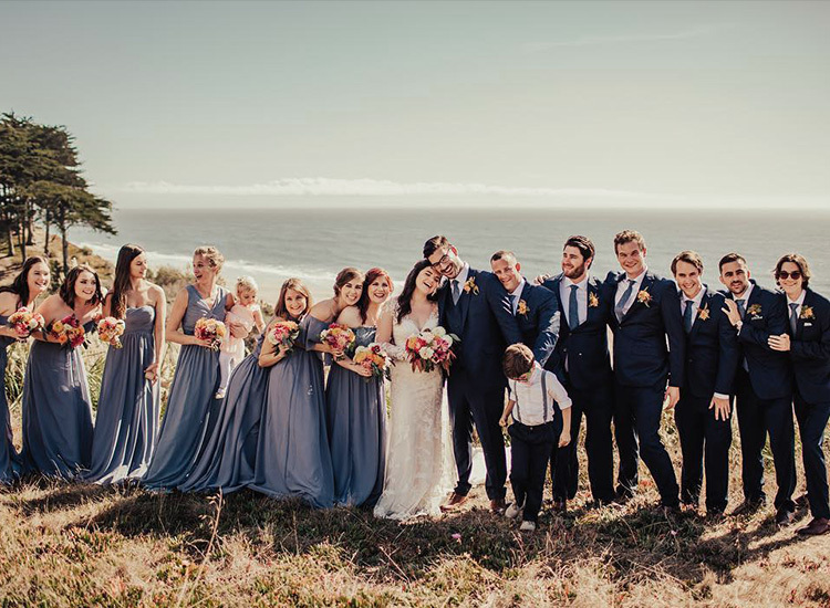 a wedding party posing on the beach
