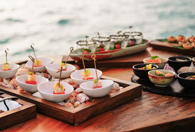 plated appetizers on individual plates on a wooden table in front of the ocean