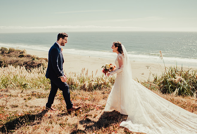 a bride and a groom standing in front of a beach