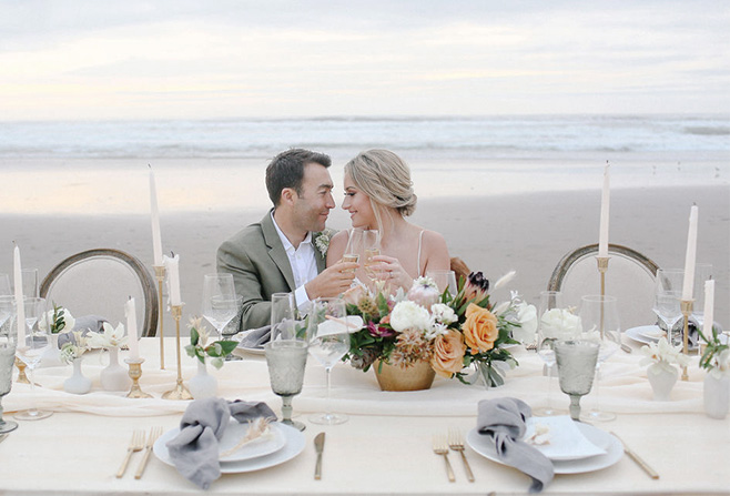a couple sitting at a table looking at each other on a beach