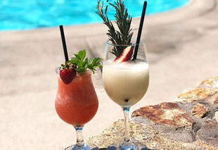 two tropical cocktails near pool