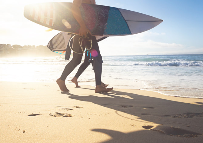 two people with surf boards on the beach