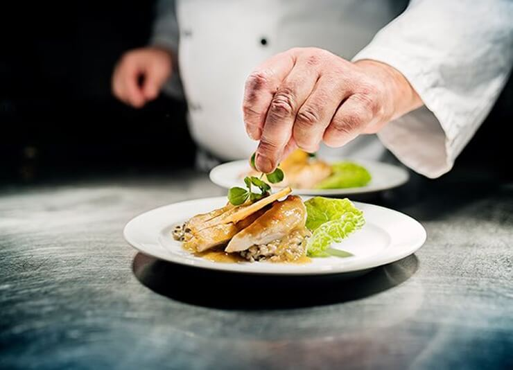 man plating a dinner plate