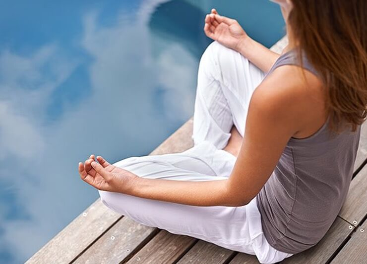 woman meditating on a dock