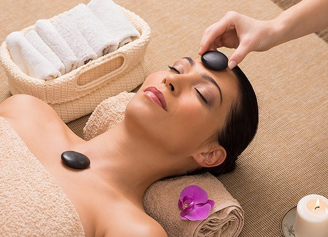 a woman getting a stone facial at the spa