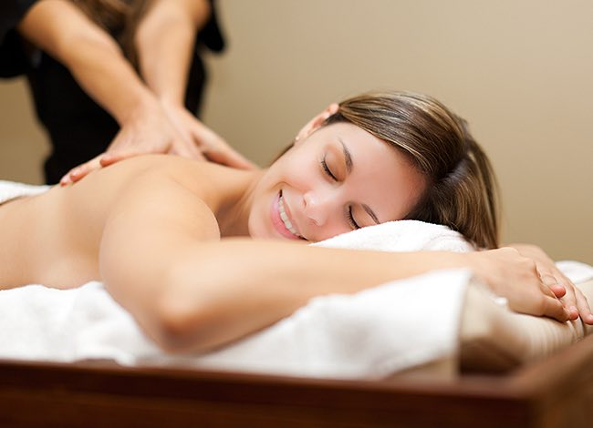 a woman smiling during her back massage