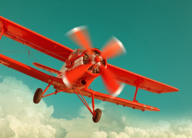 retro red biplane in the sky