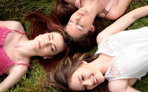 girls lying in grass