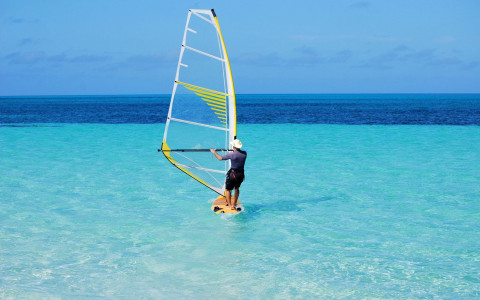 Man windsurfing on bright blue ocean water