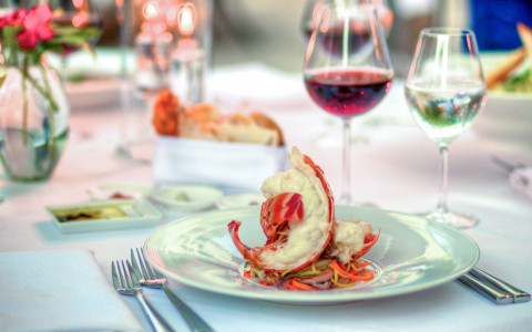 Lobster on white plate with two glasses of wine