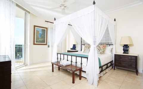 Guest room with canopy bed and balcony