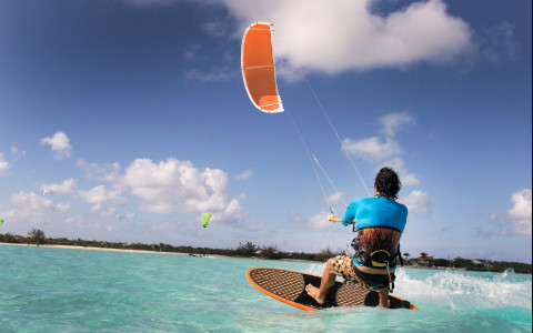 Man kiteboarding on ocean with beach in background