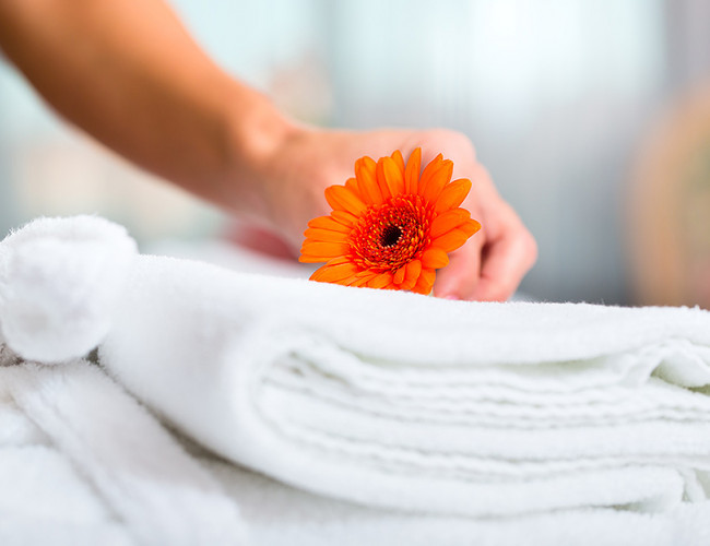Hand placing an orange flower onto a pile of folded white towels