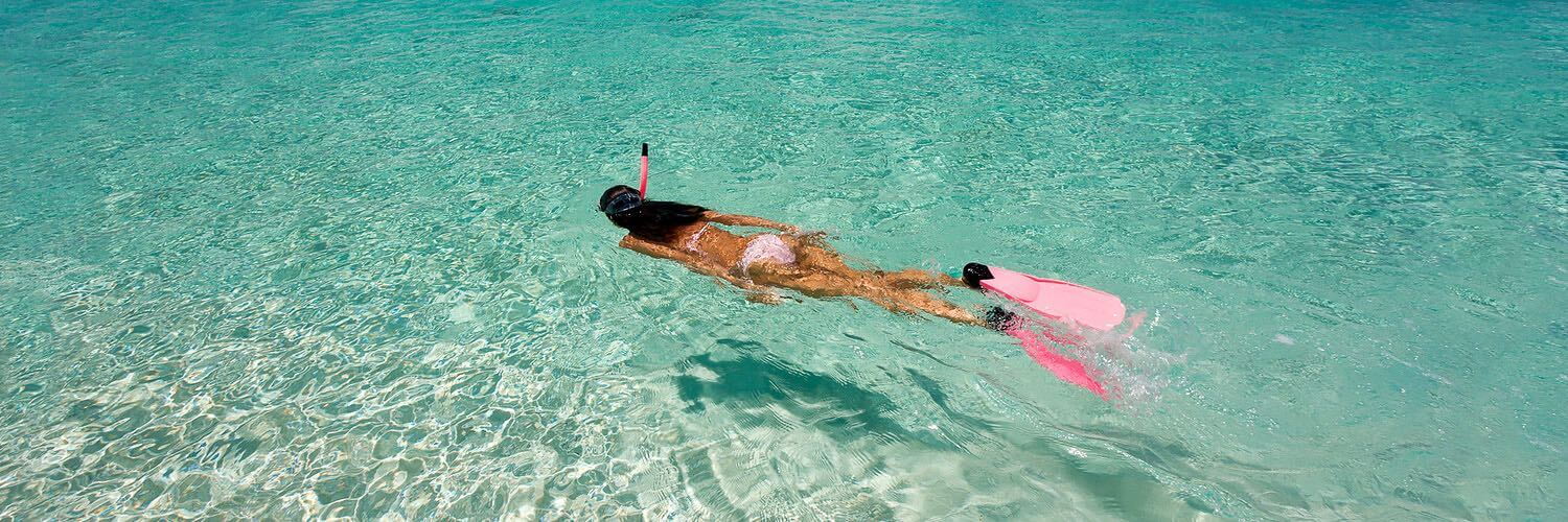 Woman snorkeling in shallow ocean water