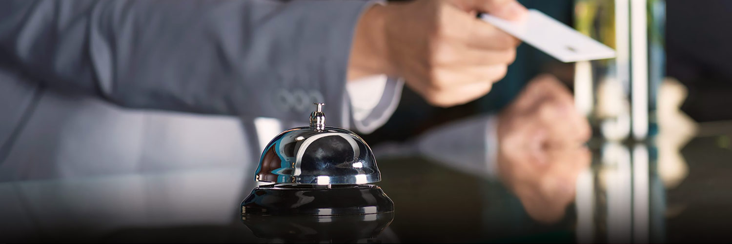 Hand with room key card and concierge bell