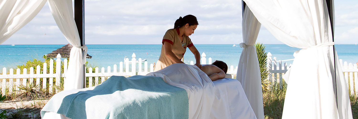Woman getting back massage by the beach