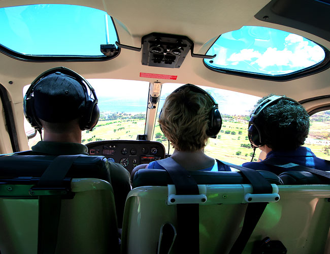 Three people in cockpit of small airplane