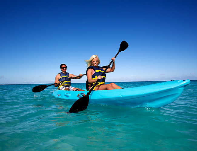 Man and woman kayaking on ocean