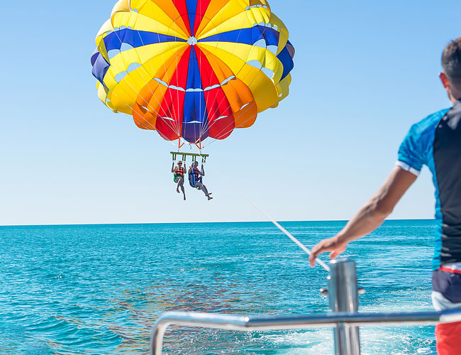 Parasailers on the back of a boat