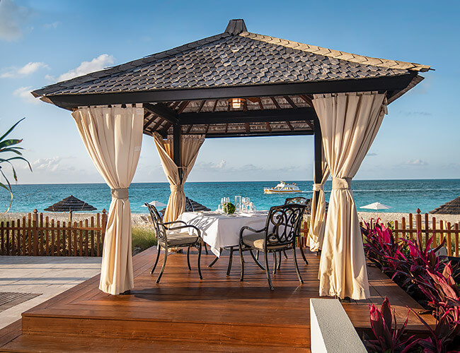private dining table under beachside cabana