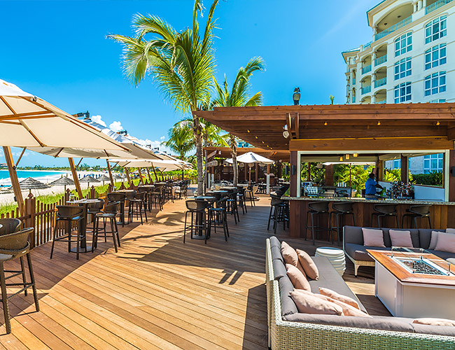 The Deck Restaurant with several table and chairs and lounge chairs with blue skies and ocean views in the background