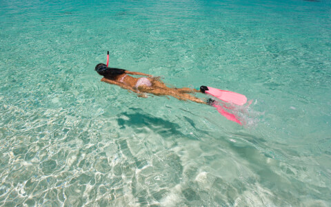 woman in pink bikini with pink flippers and snorkels snorkeling in clear blue water