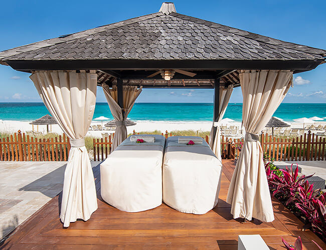 couple massage tables under beachside cabana