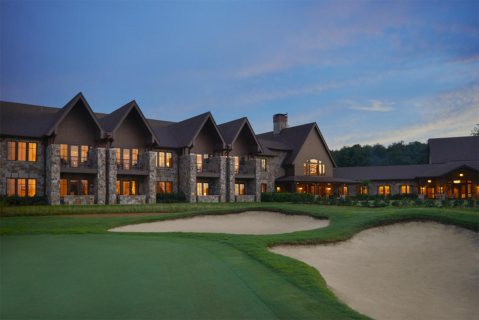 exterior of property at night with golf course in front