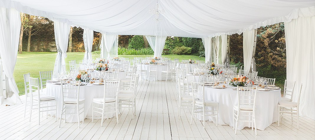 Outdoor wedding set up with white decor and canopy