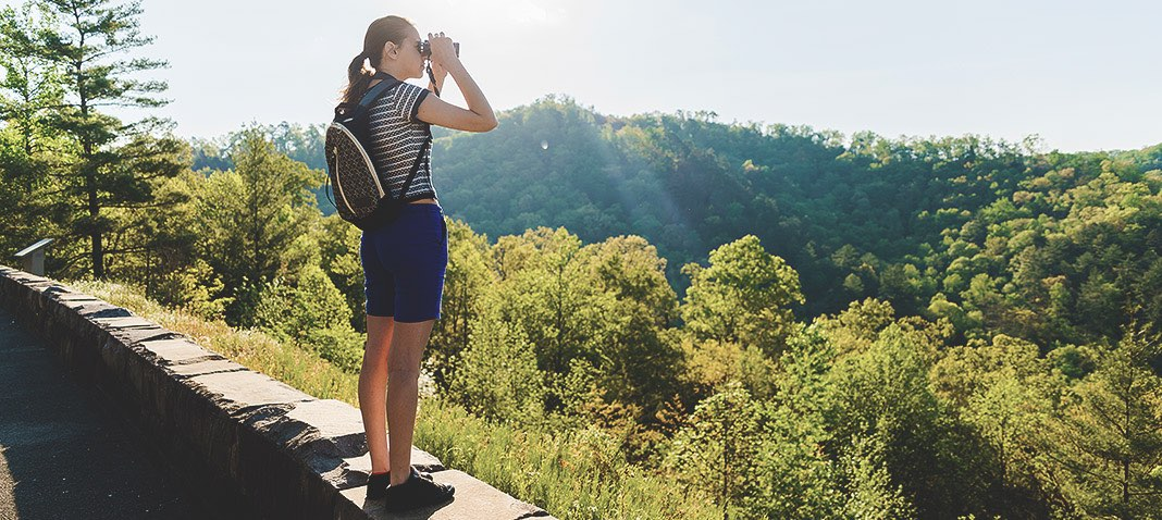 Woman looking at nature through binoculars