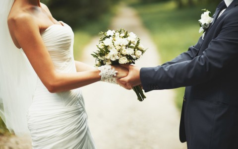 Wedding couple holding flower bouquet