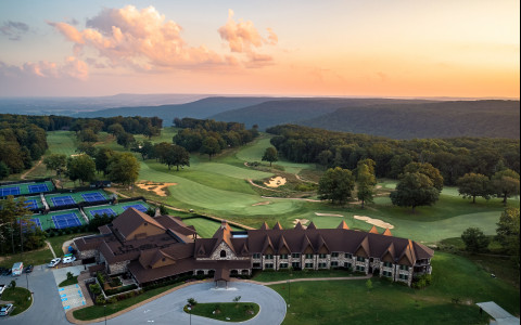 drone view of sewanee hotel with green landscape and tennis courts behind it