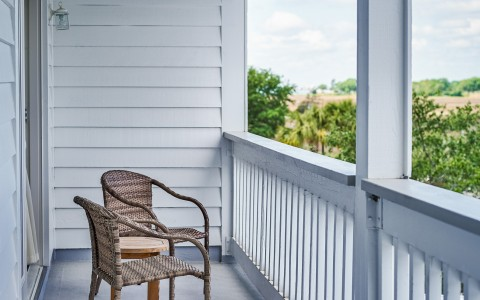 White balcony with brown chairs