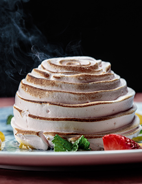 A tall swirled chocolate dessert with steam coming off the top