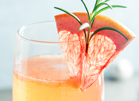 A cocktail garnished with a grapefruit and greenery on the side of the cup
