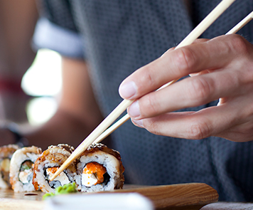 Close up of a person's handing using chopsticks to pick up a roll of sushi
