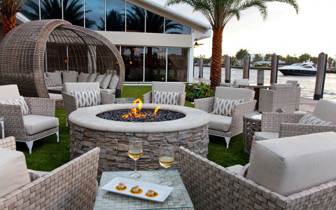 Cushioned outdoor chairs surround a circular outdoor fire pit with a circular wicker covered couch in the rear