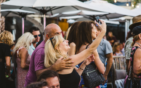 A man and woman taking a selfie on the outdoor patio area surrounded by other people mingling