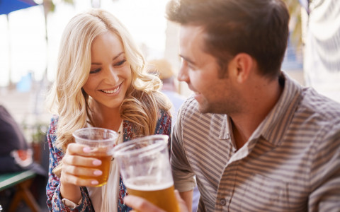 A man and a woman holding a cup of beer smiling at each other