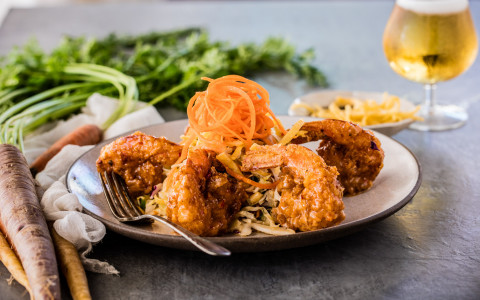A small plate of fried shrimp with a stack of carrot shavings in the center